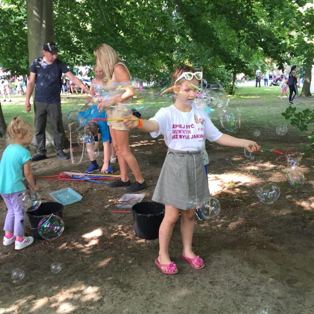 Zdjęcie. Na zdjęciu dziewczynka w parku, w białej koszulce z logo FREE robiąca bańki mydlane, w tle inni ludzie